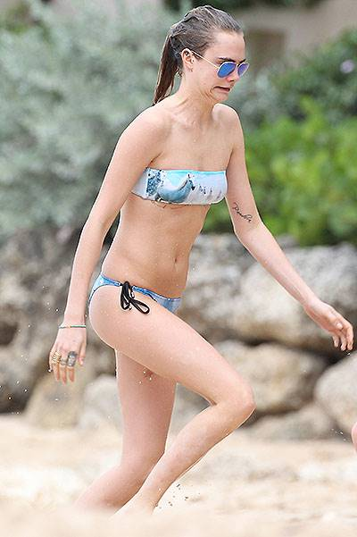 Cara Delevingne is pictured at the beach playing football