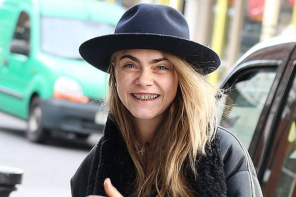EXCLUSIVE: Gold toothed Cara Delevingne sports a 'grill' as she heads out with pal Michelle Rodriguez in Notting Hill  on February 1, 2014