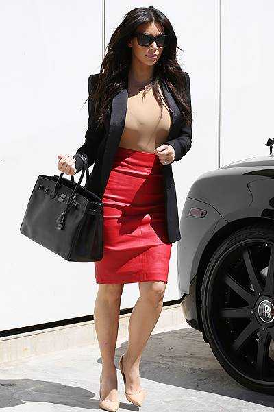 Kim Kardashian is seen leaving Kanye West's Hollywood home in a red leather skirt