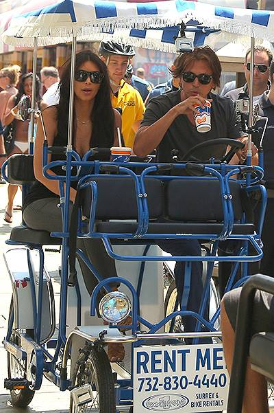 Kim Kardashian and Jonathan Cheban smile for the fans at Seaside Heights as they ride the swings and drive a covered bicycle on the boardwalk