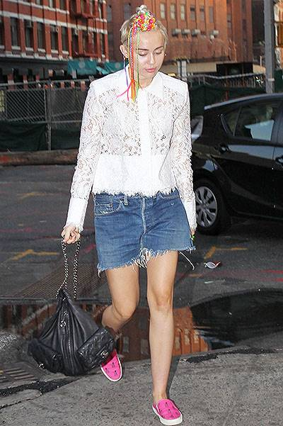 Miley Cyrus with funky beads in her hair and interesting outfit