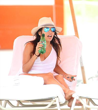 Eva Longoria smiles in a white bikini and white playsuit at the beach in Miami